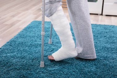 Man With Broken Leg Using Crutches For Walking On Blue Carpet