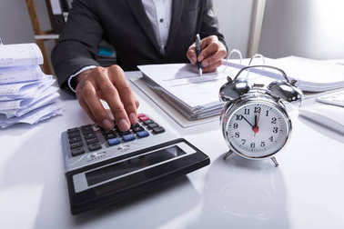 Businessperson Using Calculator For Calculating Bill With Alarm Clock On Desk