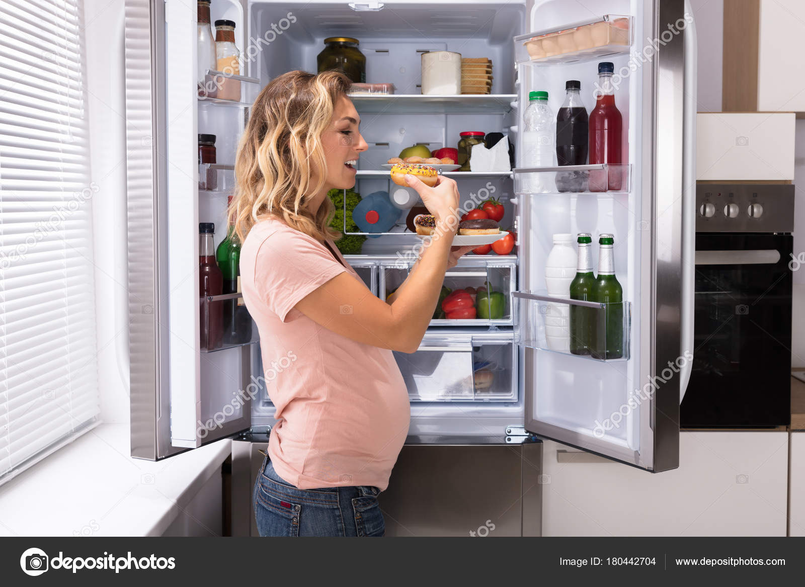 Kühlschrank Planer : Glücklich schwangeren frauen essen donut vor offenen kühlschrank und