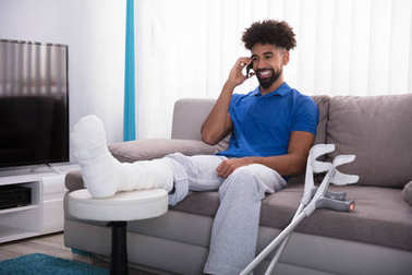 Happy Young Man With Broken Leg Sitting On Sofa Talking On Mobile Phone