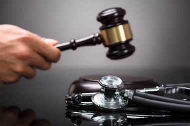Judge's Hand Striking Gavel With Stethoscope On Desk