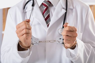 Close-up Of Arrested Doctor's Hand With Handcuffs