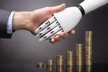 Businessperson And Robot Shaking Hands Over Stacked Golden Coins
