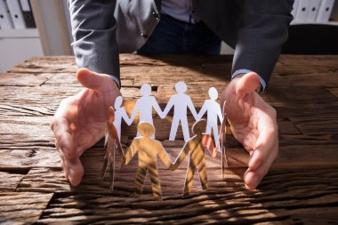 Businessperson's Hand Protecting Paper Cut Out Figures On Wooden Desk