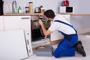 Male Technician Examining Dishwasher With Digital Multimeter