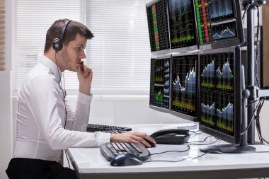 Side View Of A Young Male Stock Market Broker Analyzing Graphs On Multiple Computer Screens