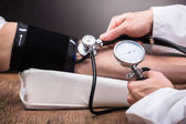 Close-up Of Doctors Hand Checking Patients Blood Pressure Over Wooden Table