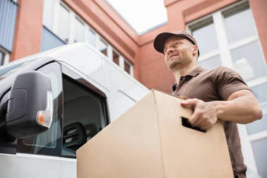 Portrait Of A Happy Young Delivery Man Carrying Cardboard Box Near Van