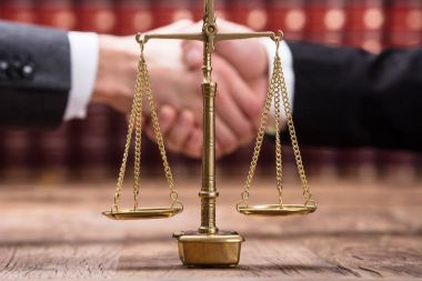 Close-up Of Justice Scale On Wooden Desk In Front Of Businesspeople Shaking Hands