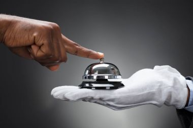 Close-up Of Customer Ringing Service Bell Held By Butler In Front Of Grey Background