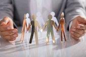 Fotografie Nahaufnahme der Unternehmer Hand schützen Papier ausgeschnitten Figur auf Tisch im Büro