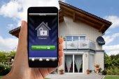 Něčí ruka drží Smartphone za odzbrojující systém zabezpečení domu