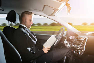 Young Businessman Sitting Inside Self Driving Car And Reading Book