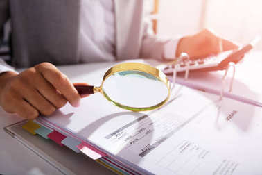 Photo Of Businesswoman Analyzing Invoice With Magnifying Glass