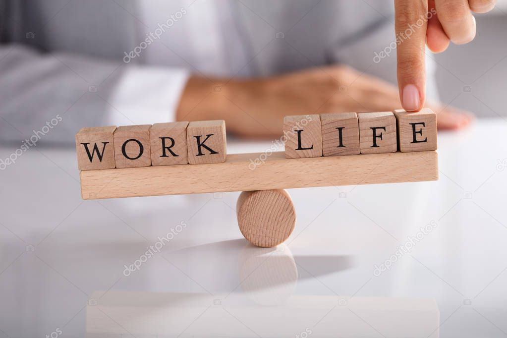 Close-up Of Businessperson's Finger Showing Imbalance Between Work And Life On Wooden Seesaw