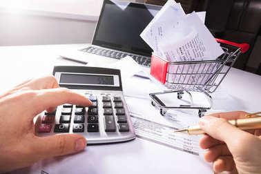 Close-up Of Person Calculating Invoice With Calculator Near Shopping Cart On Desk