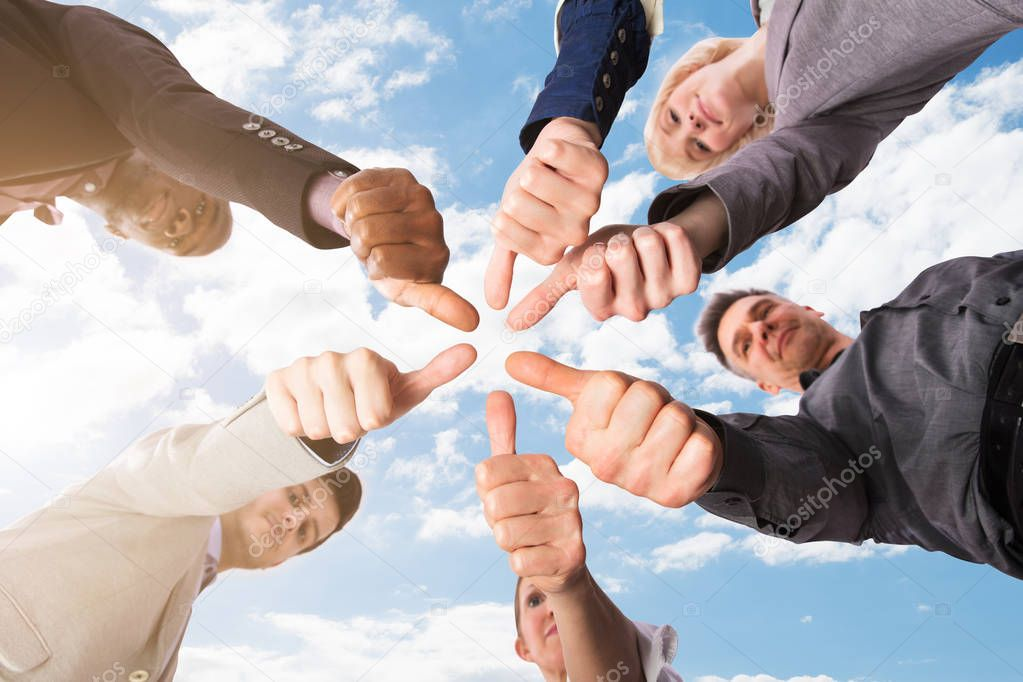 Low Section View Of Businesspeople Gesturing Thumbs Up Against Sky