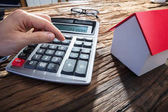 Fotografie Persons Hand Using Calculator With House Model On Wooden Desk