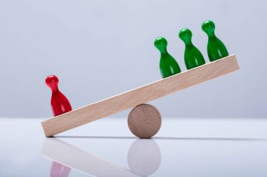 Red And Green Pawns Figures Balancing On Wooden Seesaw Over The Desk
