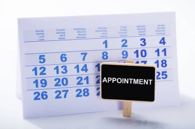 Miniature Appointment Placard In Front Of Calendar Against White Background