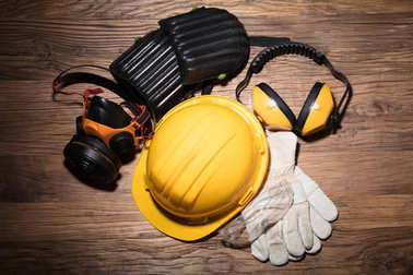 Close-up Of Yellow Hard Hat With Safety Equipment On Wooden Background stock vector