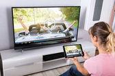Fényképek Fiatal nő segítségével a digitális tábla, hogy tévénézés a nappali szobában