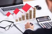 Podnikatel, výpočet daně před dům modely a skládaný mincí brýle a kalkulačka