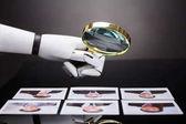 Fotografie Detail robota ruky při pohledu na fotografii kandidáta s lupou