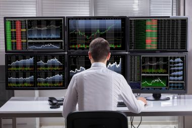 Side View Of A Young Male Stock Market Broker Analyzing Graphs On Multiple Computer Screens stock vector