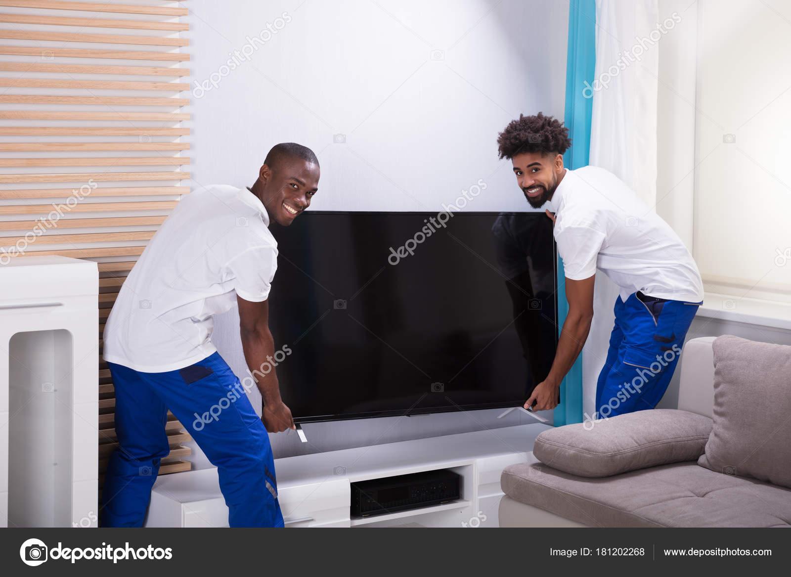 Porträt Von Zwei Lächelnde Junge Männliche Movers, Platzieren Den Fernseher  Im Wohnzimmer U2014 Foto Von AndreyPopov