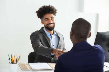Smiling Young Businessman Shaking Hand With Male Candidate In Office