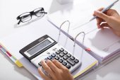 Fotografie Close-up Of Businessperson Calculating Bills With Calculator In Office