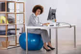 Fotografie Businesswoman Sitting On Fitness Ball Working On Computer