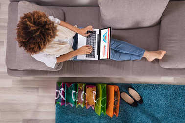 Happy Young Woman Using Laptop With Multi Colored Shopping Bags On Carpet