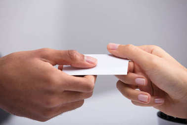Close-up Of Two Businesspeople Hand Holding Blank White Card