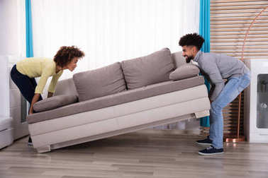 Side View Of Young Smiling Couple Lifting Sofa In Living Room