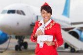 Fotografia Ritratto di una giovane hostess sorridente di fronte dellaeroplano