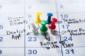 Fotografia Puntine da disegno colorati bloccati sul calendario con importante appuntamento scritto su di esso