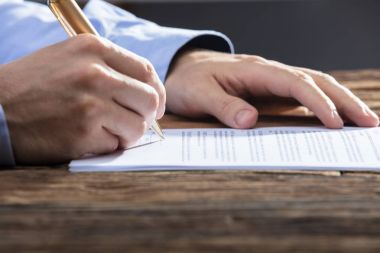 Close-up Of A Businessperson's Hand Signing Document On Wooden Desk