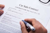 Photo Close-up Of A Persons Hand Filling Car Sale Contract Form