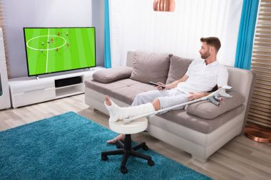 Young Man With Broken Leg Sitting On Sofa Watching Football Match On Television