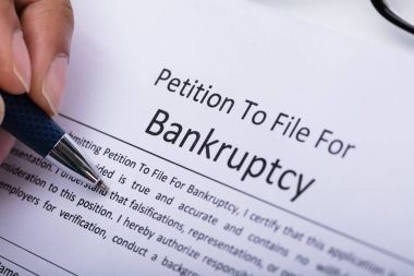 Close-up Of A Person's Hand Filling Bankruptcy Form