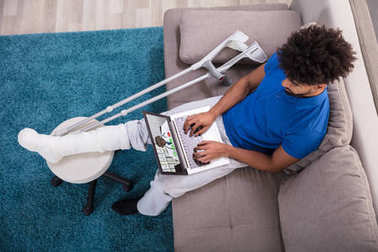 High Angle View Of A Young Man Sitting On Sofa Video Conferencing With Doctor