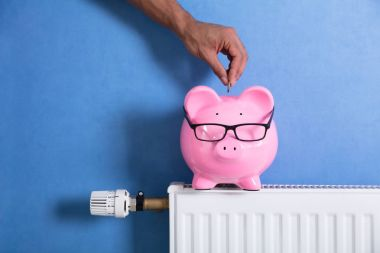 A Person's Hand Adjusting Thermostat With Piggy Bank On Radiator