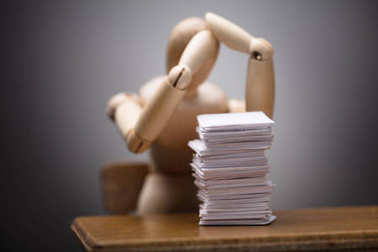 Wooden Dummy Figure Suffering From Headache Sitting On Chair With Stack Of Documents On Desk