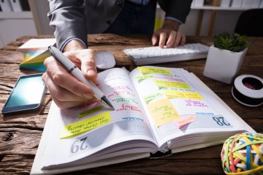 Close-up Of A Businessperson's Hand Writing Schedule In Diary With Pen On Wooden Desk