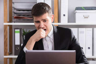 Close-up Of A Worried Businessman Looking At Laptop In Office
