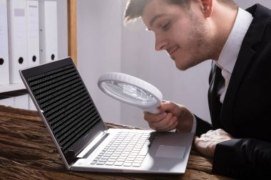 Young Businessman Looking At Binary Code With Magnifying Glass On Wooden Desk