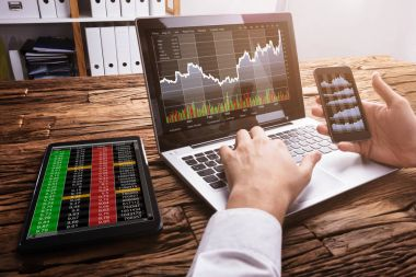Close-up Of A Stock Market Broker Working With Graphs On Laptop At Workplace