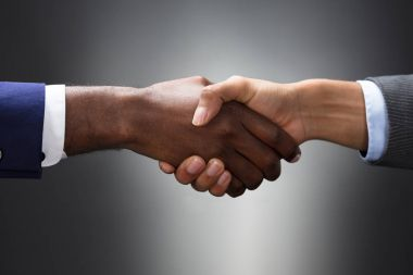 Close-up Of Multiethnic Hands Shaking Against Gray Background